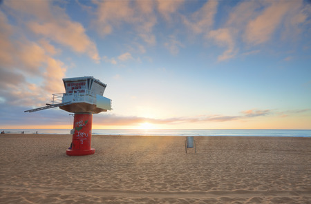 The sun rises at Avoca Beach NSW Australia.   A vandalised lifeguard tower stands to the left photo