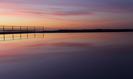 envelops: Beautiful sunrise and tranquil reflections at Wombarra.  Stand still in quietude  while natures stunning beauty envelops you and purifies the soul purging your mind of inner stresses and turmoil.   Breath.
