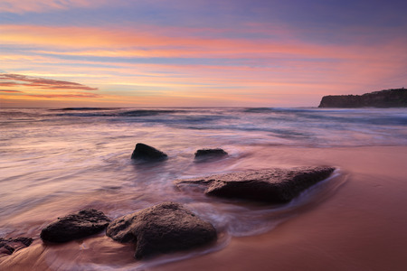 Intense summer sunrise colours at Bungan Beach and mesmerising ocean flows.  The beach is backed by 40m headland, with steep access and limited parking, this beach never gets crowded but attracts surfers with 1.5m average waves.  Permanent visible rips to