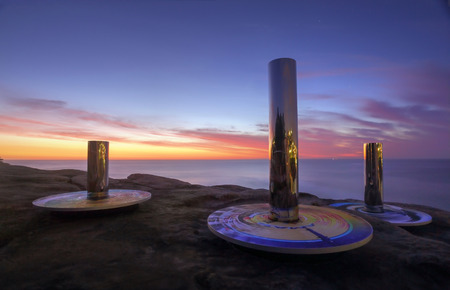 linda: BONDI, AUSTRALIA - OCTOBER 23, 2014; Sculpture by the Sea .  Sculpture titled Coast Totem by Linda Matthews and Carterwilliamson , against a spectacular beautiful sunrise sky at Bondi.  Made from chrome, steel, synthetic rubber