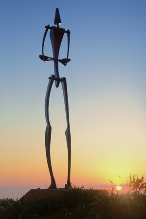 titled: BONDI, AUSTRALIA -  NOVEMBER 9, 2014; Sculpture by the Sea free public event 2014.  The sun rises on the horizon behind sculpture titled Big Man  by Will Maquire, NSW  Made of hot forged steel.   Note ISO 8000 used
