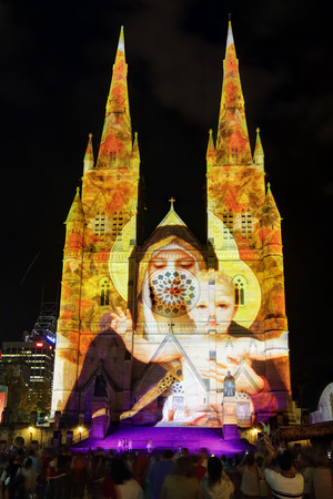 crowds of people: SYDNEY, AUSTRALIA - DECEMBER 23, 2014; Crowds of people on the forecourt of St Marys Cathedral Sydney CBD watch and enjoy the Christmas lights display.  Madonna and Child one of the many visions on display on the church building sandstone facade at Chris
