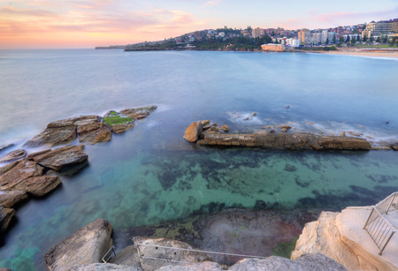 giles: The view from the headland down into Giles Baths rockpool at Coogee in a mid tide.  At low tide the rockshelf at bottom of stairs will become exposed.  Long exposure taken at sunrise.  There is notion in the water and over the rocks.  Coogee is a popular