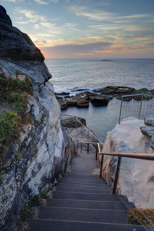 cliff face: Steep stairs lead down the cliff face to Giles Baths rockpool on the northern end of Coogee, Sydney Australia.
