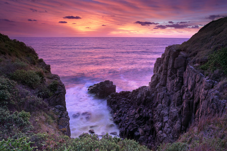 vibrant colours: Fiery red and orange sunrise skies bath the ocean and Minamurra volcanic  landscape cliffs in beautiful rich and vibrant colours Stock Photo
