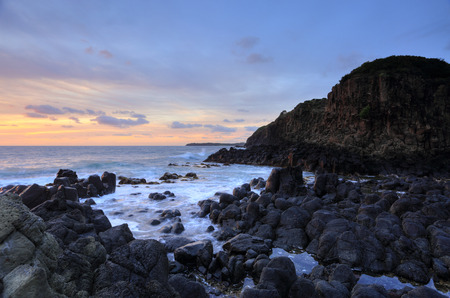 Sunrise skies  of soft pretty colours at bottom of the Minamurra volcanic landscape cliffs at low tide Stock Photo