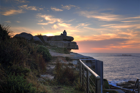 dog rock: A woman and her dog watch the sunrise from a high rock at Coogee North side headland.  The best way to start the day Stock Photo
