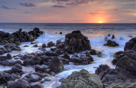 Sunrise over the Minamurra rugged, craggy volcanic rocks and ocean flows at low tide