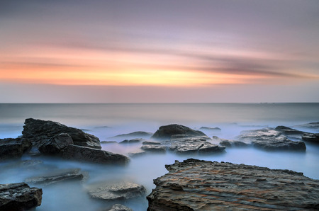 Sunrise and rocks at Coogee Beach long exposure showing movement in clouds and ocean.