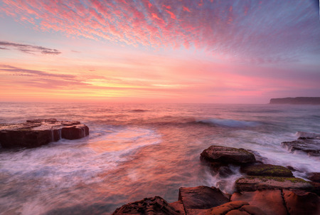 Summer sunrise skies  light up with colour throwing warmth across the  landscape and whitewater seas wash around the rocks at North Avoca Central Coast NSW Australia