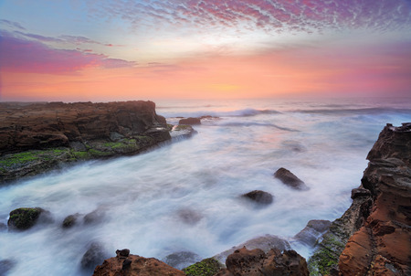 sunup: Break of dawn the rosy flamingo feathered sunrise skies compete for attention with turbulent rushing ocean flows over tidal rocks