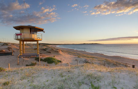 lifesaving: Early summer morning  at Wanda beach with golden sunlight falling on the Wanda  surf lifeguard tower
