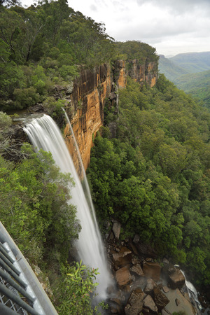 fitzroy: Views of Fitzroy Falls from the grated balcony lookout at the top of the escarpment with a downward perspective capturing the first of the spectacular falls iover sheer vertical cliffs nto the eucalypt forests of the valleys below.  Morton National Park. Stock Photo