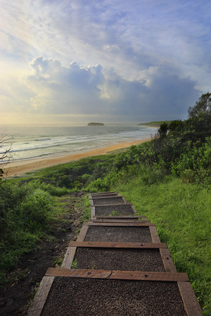 headland: The timber and bitumen  path abruptly ends from the headland at Mystics Beach in Killalea State Park, then you make your own way down through the trees and vegetation.  Misty salt spray, filtered sunlight and breaking surf sure give this beach a mystical  Stock Photo