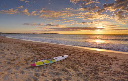 paddleboard: Beach sunrise and paddleboard on the sand  at shoreline.