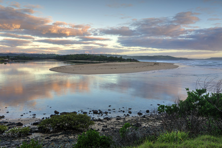 south coast: Picturesque sunrise as Minamurra river meets the ocean entrance and reflections in its waters.  South Coast NSW Austtralia.