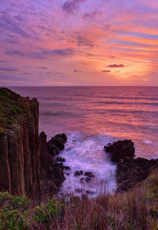 kiama: Beautiful sunrise over the ocean with volcanic sea cliffs rising up
