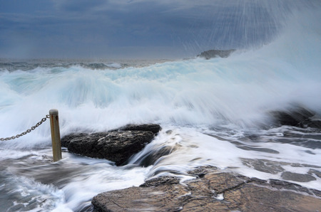 orificio nasal: Preparándose para las grandes olas poderosas rompiendo sobre las rocas en Blowhole Point Rock Pool