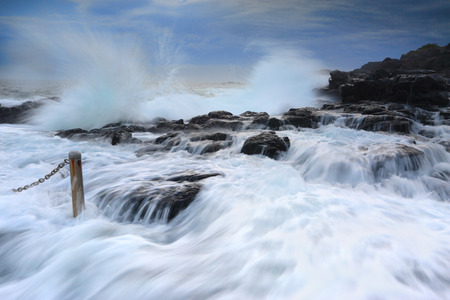kiama: High tide and waves crashing onto the rocks bringing strong fast flowing water over the rocks and gushing past me into the rock pool at Kiama