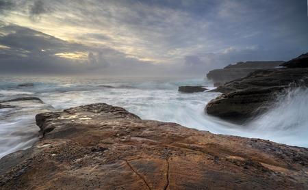 lashing: Moody sunrise and wild waves lashing the coast at Little Bay NSW Australia.
