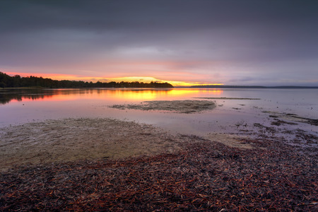 georges: Clouds closed in the skies in the late afternoon.  Standing in rain with my dog to capture the only colour to the south west and a blush of colour on the clouds and reflections in the pristine waters of St Georges Basin Sanctuary Point. Stock Photo