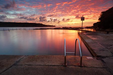 headland: Beautiful red sunrise over Malabar Ocean Rockpool in Long Bay near Sydney Australia