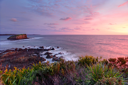headland: Pretty clouds light up at sunrise with views from the Minamurra headland overlooking the exposed volcanic rocks below and Stack Island