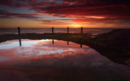 invigorate: Spoilt this morning with a spectacular sunrise full of vivid colours painting the sky with reds and oranges and blues.  This   natural rockpool at South Coogee in Sydneys eastern suburbs reflecting the mornings colours in the sky and clouds for a triple Stock Photo