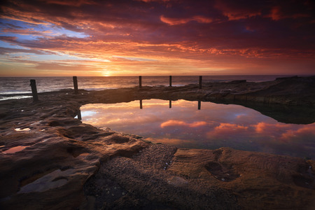 intresting: The Ivo Rowe pool is a natural rockpool fed by the ocean in high tide.  Its eroded rocks and weathered timber and chaim fence  are intresting features.   The stunning sunrise of reds and oranges in the sky colours its tranquil waters and highlights the r