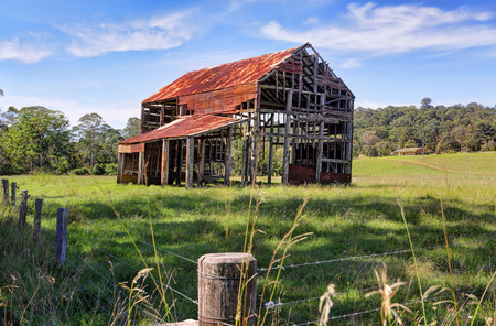 disrepair: This old ramshackle rustic glory a once grand two storey barn with corrugated roof and timber trusses now just a skeleton of what it formerly was, its purpose no longer needed it is left abandoned to decay and disrepair.  The farmland was once used as a p