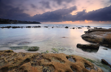 headland: Bronte Beach at dawn before the sunrise, urban lights visible on the headland as the moody clouds and sky showing hints of the orange colour to come, in the foreground the weathered eroded rocks have formed craters and beyond the beautiful aqua hues of th
