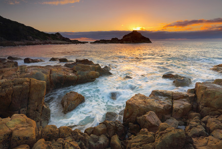 columnar: Sun rising behind Mimosa Rocks, the geology here is varied and includes various volcanics, mixed with mudstone, interesting sea stacks and columnar jointing. Stock Photo