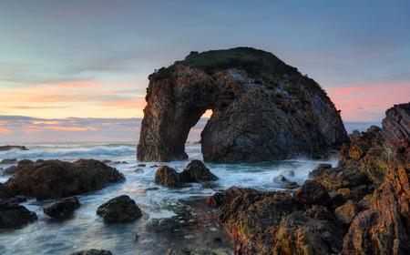 Horse Head Rock al amanecer. Una formación de roca natural que se ha erosionado con el tiempo en la forma y apariencia de un agua potable de caballo. La roca se encuentra en una playa de guijarros aislado en Bermagui, costa sur de NSW, Australia Foto de archivo - 39059707