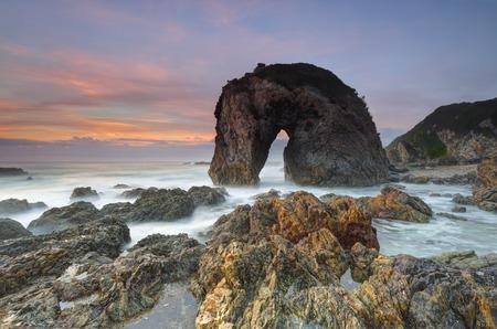 caballo de mar: La magnífica estructura natural de la roca, la cabeza de caballo de la roca, que se encuentra en el hermoso pueblo de pescadores de la costa de Bermagui. La roca ha resistido por las fuerzas de la naturaleza a través del tiempo y se asemeja a un agua potable caballo. Detrás del cielo se ilumina en tonos de