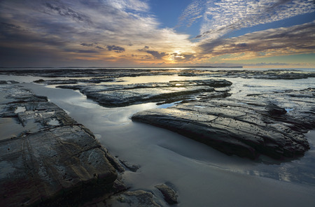 australia landscape: The light from the sun filtered through high cloud just after sunrise falls across the  rocks wet sand and shallow tidal flows at Plantation Point, Vincentia in Jervis Bay creating interesting ares of light and dark.  Beecroft Peninusla in the far horizon Stock Photo