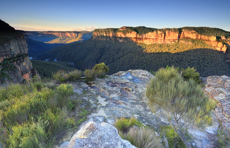 bushwalk: Early morning sunlight strikes the southern walls at Walls Lookout in the Blue Mountains National Park.  There is a small amount of fog in the valley and on the clifftop some puddles from earlier rain. Stock Photo