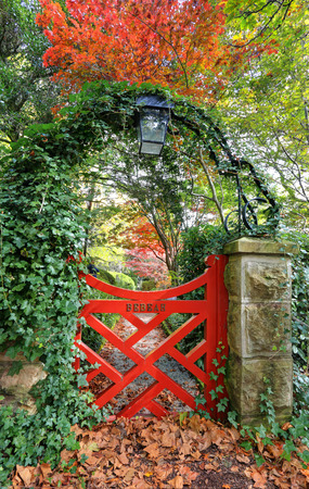 vistas: The little red gate at Bebeah Gardens in Autumn.  The parklands were originally built by Edward Cox in 1880.  Sprawling over many acres the garden includes various vistas of formal country garden. Mt Wilson Stock Photo