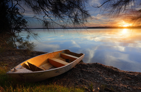 sublime: Sublime scene and tranquil waters reflecting like a mirror as the divine sun sets casting its golden orange glow upon the clouds and highlighting the little boat as it rests on the shoreline, waiting for tomorrows dreams and adventures.  If you want to ge