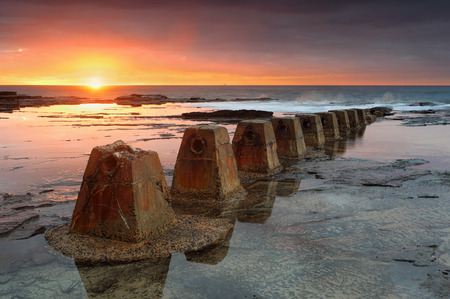 tasman: The sun rises at Coledale, casting its warm colours over the rockshelf with weathered and textured old pipeline holders in foreground.  There is a ship on the horizon.