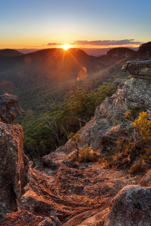 gully: The last rays of sunshine stream over Wilsons Gully and the valley and highlight the foreground cliffs and rock ledges and foliage.  Sunset views from Sunset Rock, Mt Victoria in the Blue Mountains, Australia