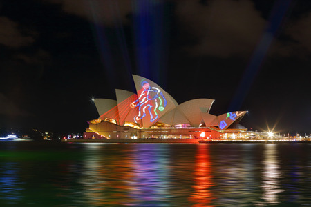 public figure: SYDNEY, AUSTRALIA - MAY 22, 2015; Sydney Opera House illuminated with light and moving pictures and imagery during the Vivid Sydney 2015 annual public event. Here an outline figure casts a red light over the sails.