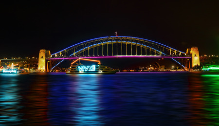 sydney harbour bridge: SYDNEY, AUSTRALIA - MAY 21, 2015; Sydney Harbour Bridge Vivid lights preview for Vivid Sydney 2015. Two boats displaying Vivid and #ilovesydney cruising on the waters near the Sydney Harbour Bridge decorated in lights for Vivid Sydney. Editorial