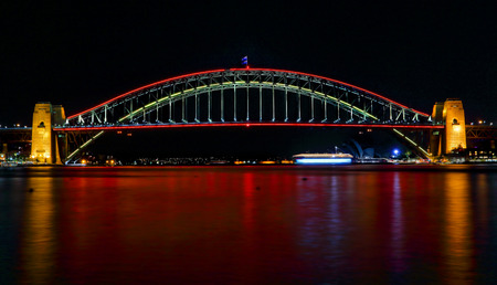 reds: SYDNEY, AUSTRALIA - MAY 21, 2015;  Sydney Harbour Bridge lights up in vivid reds for Vivid Sydney 2015 and a harbour of vivid red water as well