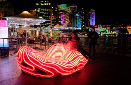 he is public: SYDNEY, AUSTRALIA - MAY 27, 2015;   The Heart of the City is designed to be both a public artwork and a catalyst for interaction between people.  A member of the public takes a seat and sensors detect a heart rhythm and the object illuminates with each he