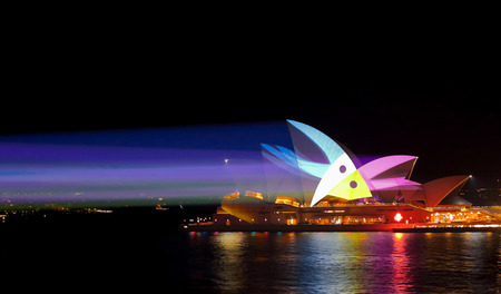 light beams: SYDNEY, AUSTRALIA - MAY 25, 2015;   Light beams stream onto the iconic landmark, the Sydney Opera House casting various moving patterns andn imagery during Vivid Sydney annual festival event. Bird like image shown.  Super high ISO to freeze the pattern
