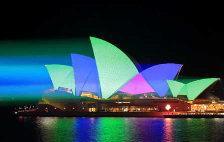light beams: SYDNEY, AUSTRALIA - MAY 25, 2015;   Light beams stream onto the iconic landmark, the Sydney Opera House illuminating it roof sails in vivid green blue and pink during Vivid Sydney annual festival event.