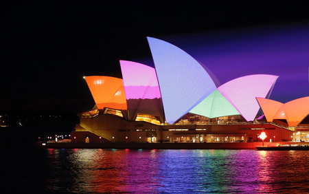 entertainment event: SYDNEY, AUSTRALIA - JUNE 2, 2015;   Sydney Opera House in bold dynamic colourful patterns for Vivid Sydney annual festival event. Prominant colours of orange pink, blue and green Editorial