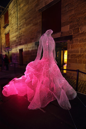 extravagant: SYDNEY, AUSTRALIA -JUNE 2, 2015;  The Dresses shapes hundreds of fibre-optic strands into the form of three beautiful and extravagant dresses. Suspended in darkness, the dresses appear as apparitions, shimmering from the realms of ethereal fantasy.  Artis Editorial