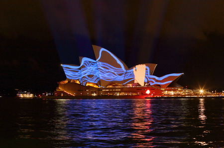 squiggles: SYDNEY, AUSTRALIA, MAY 22, 2015;  Hand grabbing blue squiggles projection image during Vivid Sydney