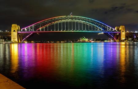 rainbow bridge: SYDNEY, AUSTRALIA - JUNE 3, 2013;  Sydney Harbour Bridge lit in vibrant rainbow colours and reflections in Sydney Harbour.  Sydney Opera House in far view.